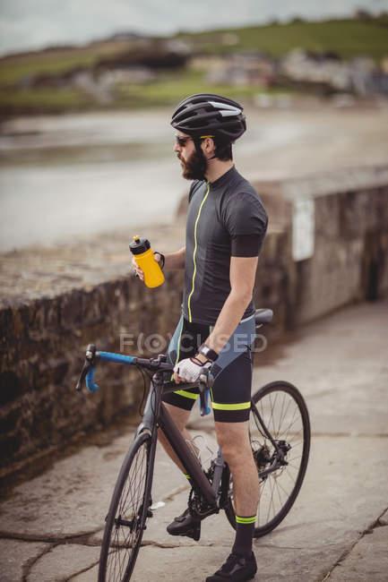 Спортсмен освіжаючий з пляшки під час велосипед їзда на дорозі — стокове фото