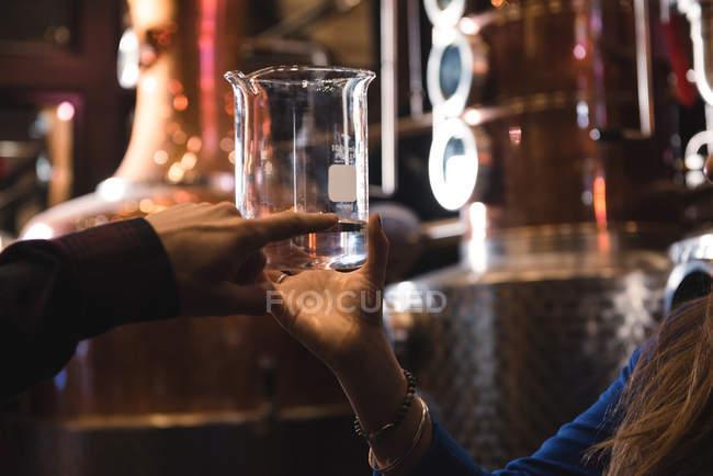 Крупным планом мужчины и женщины, изучение образца алкоголя в пивоваренный завод — стоковое фото