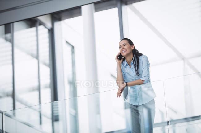 Businesswoman talking on mobile phone inside office building — Stock Photo