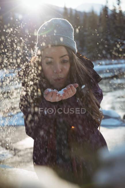 Зимой женщина выдувает снег за рекой — стоковое фото