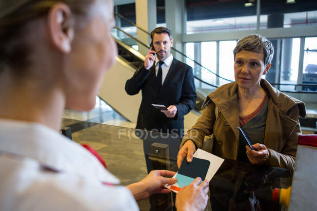 Female staff giving boarding pass to the passenger at the check in desk — Stock Photo