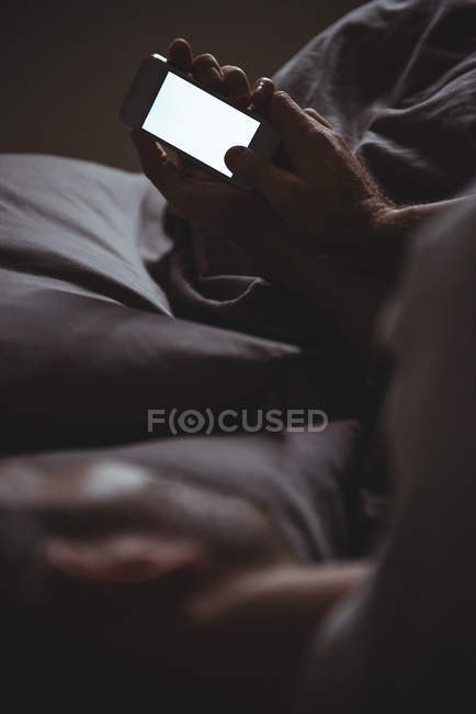 Man using his mobile phone while relaxing on bed at home — Stock Photo