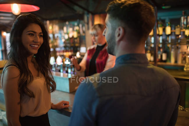 Smiling friends interacting at counter in bar — Stock Photo