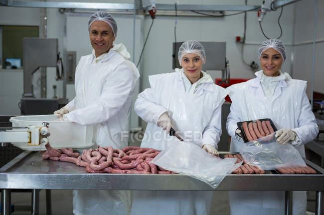 Жіночі та чоловічі м'ясників, упаковка ковбаски на заводі м'яса — стокове фото