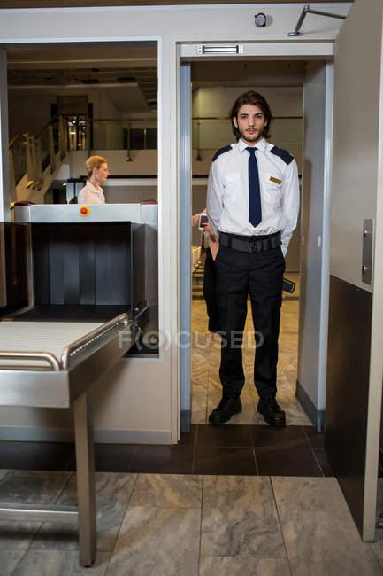 Guardia de seguridad parado debajo de la puerta de escaneo en la terminal del aeropuerto - foto de stock
