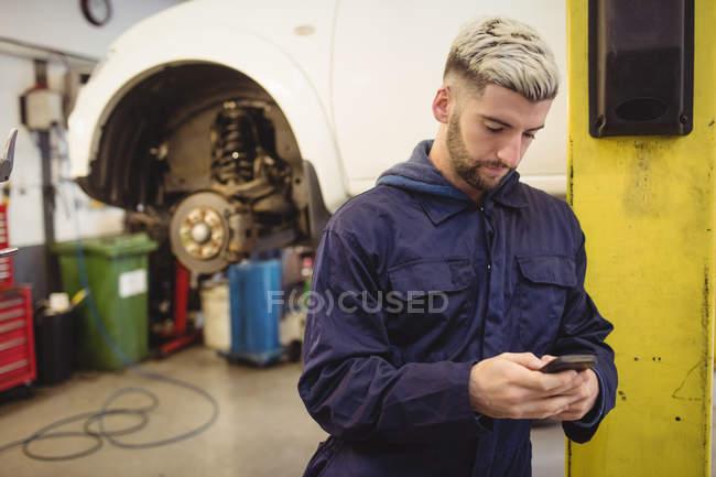Mecánico utilizando el teléfono móvil en el garaje de reparación - foto de stock