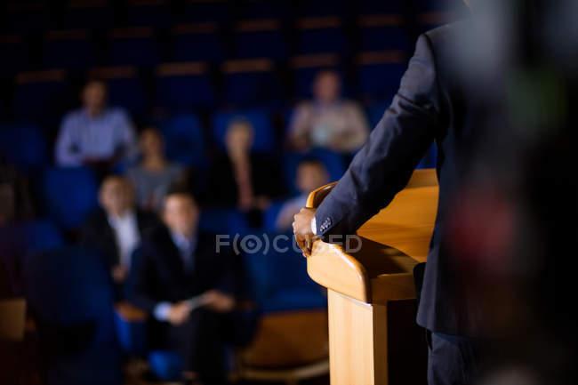 Seção intermediária do executivo masculino de negócios dando um discurso no centro de conferências — Fotografia de Stock