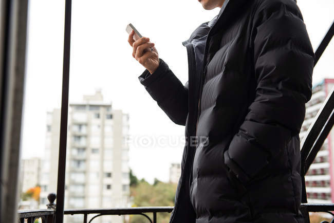 Mid-section of man using mobile phone in balcony — Stock Photo