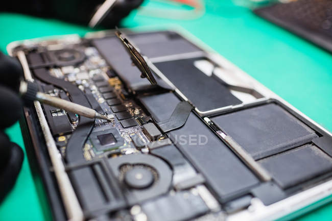 Close-up of microchip being fixed on a circuit board using soldering iron — Stock Photo