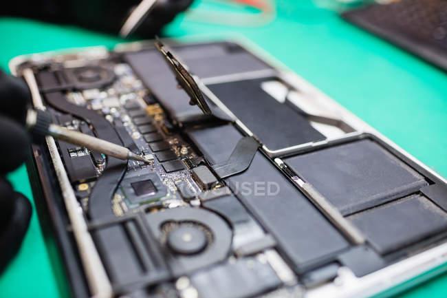 Close-up de microchip sendo fixado em uma placa de circuito usando ferro de solda — Fotografia de Stock