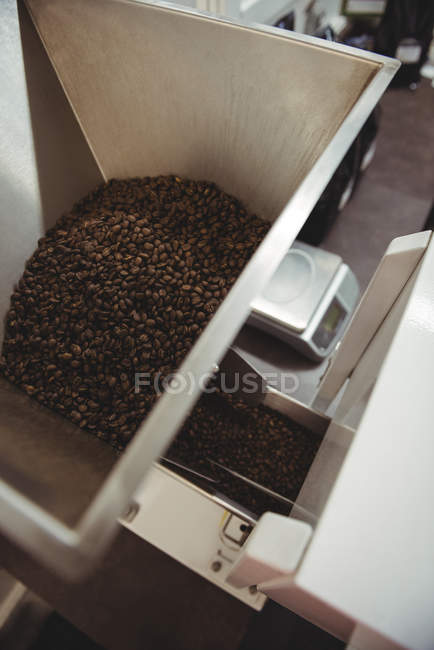Coffee beans poured inside coffee roasting machine in coffee shop — Stock Photo