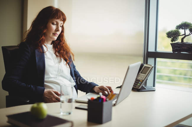 Pregnant businesswoman touching belly while using laptop in office — Stock Photo