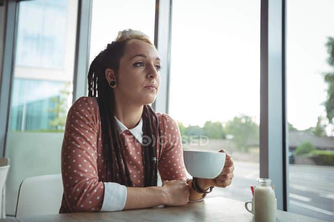 Продуманий одна жінка, чашка кави в кафе — стокове фото