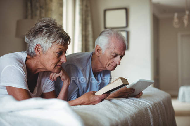 Senior woman reading a book and senior man looking at digital tablet on bed in bed room — Stock Photo