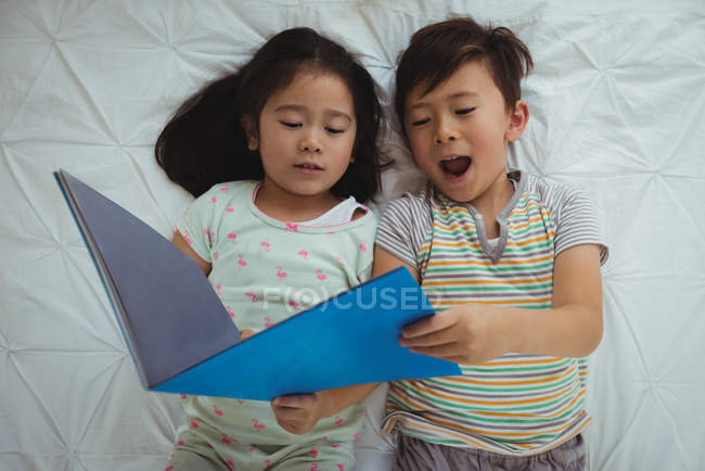 Hermanos de mentira y de la lectura del libro en el dormitorio en casa - foto de stock