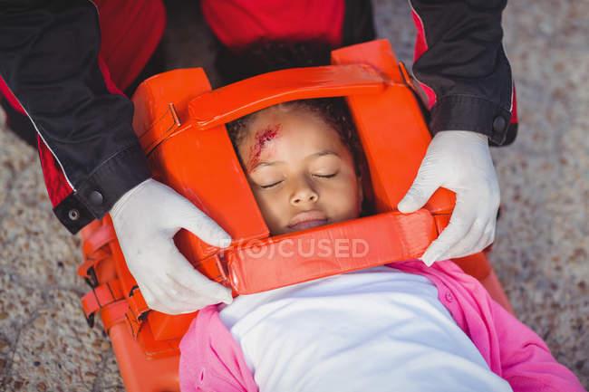 Menina ferida tratada por paramédico no local do acidente — Fotografia de Stock