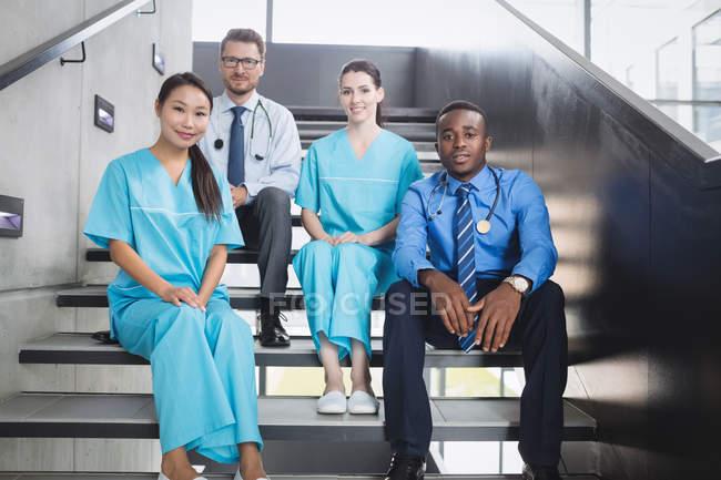 Retrato de sonriente a médicos y enfermeras sentado en la escalera en el hospital - foto de stock