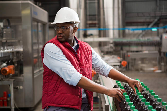 Serious male worker arranging juice bottles in factory — Stock Photo