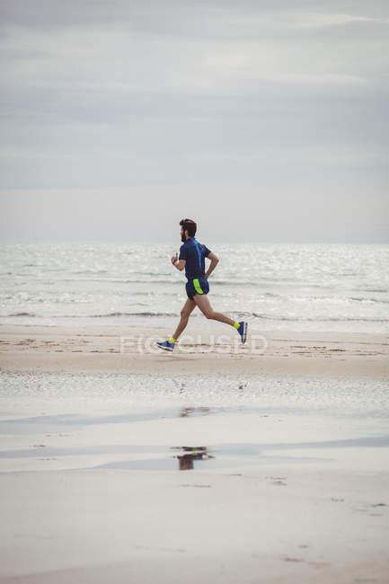 Спортсмен бегает по пляжу с мокрым песком — стоковое фото