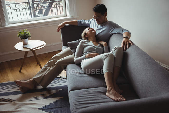 Romantic couple on sofa interacting with each other at home — Stock Photo