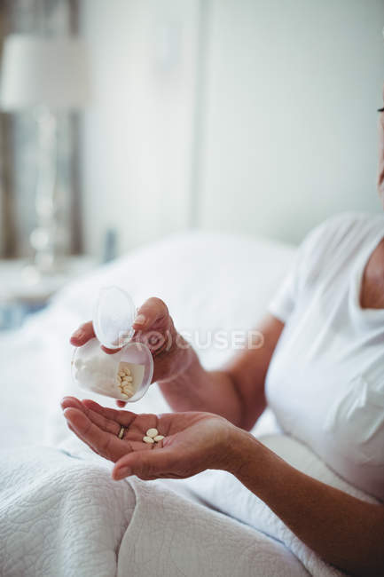 Mid section of senior woman taking medicine in bedroom at home — Stock Photo