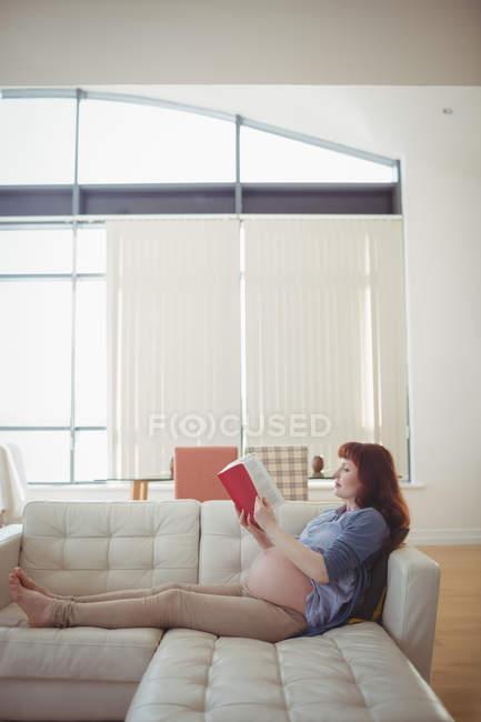 Беременная женщина читает книгу на диване в гостиной дома — стоковое фото