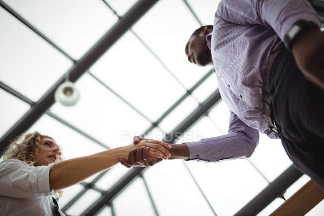 Низкий угол обзора бизнес-руководителей, пожимающих руки в офисном коридоре — стоковое фото