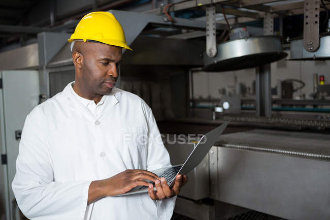 Serious male worker wearing lab coat while using laptop in juice factory - foto de stock