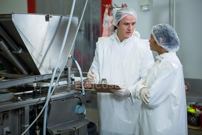 Мужчины и женщины-мясники взаимодействуют на мясокомбинате — стоковое фото