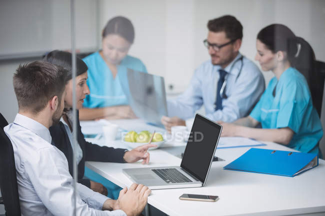 Doctors discussing over laptop in meeting at conference room — Stock Photo