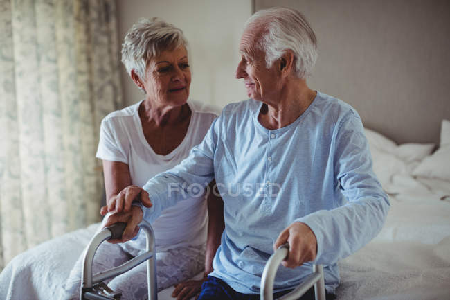 Senior woman helping senior man to walk with walker at home — Stock Photo