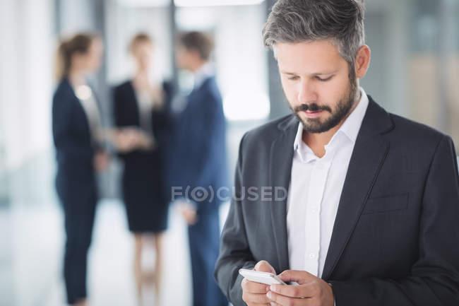 Бизнесмен с помощью мобильного телефона внутри офисного здания — стоковое фото