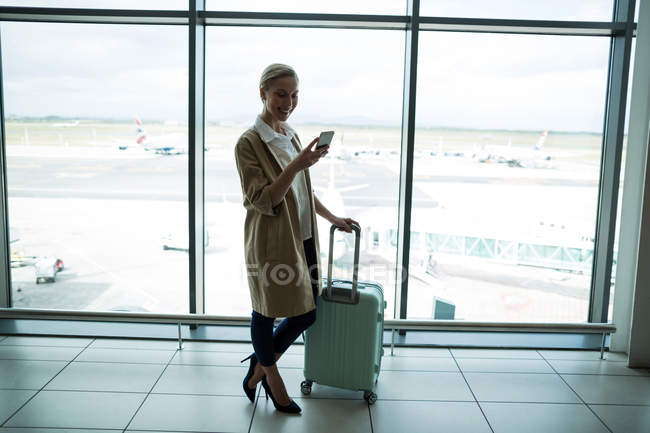 Businesswoman with luggage using mobile phone at airport — Stock Photo