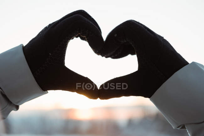 Close up of hand making a heart shape against sunrise — Stock Photo