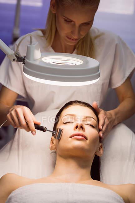 Женщины дерматологом выполнения лазерного удаления волос на лице пациента в клинике — стоковое фото