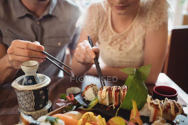 Середине разделе пары, имеющие суши в ресторане — стоковое фото