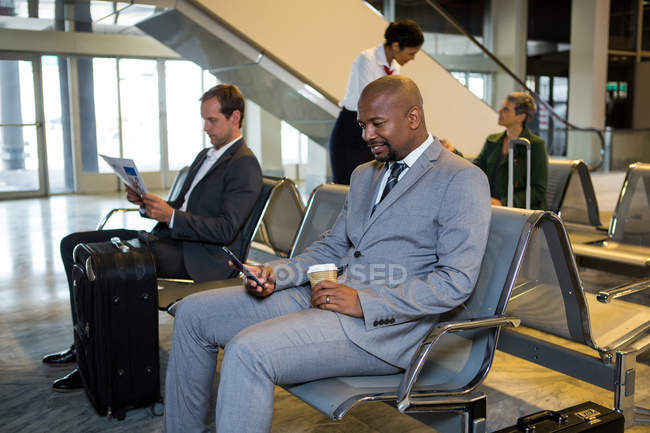 Businessman using mobile phone in waiting area at airport terminal — Stock Photo