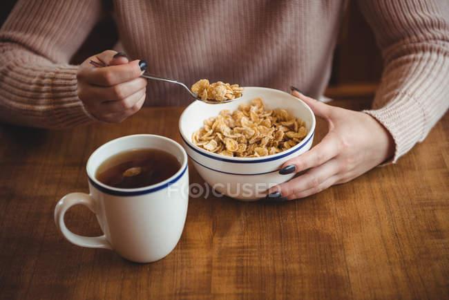 Femme ayant des céréales dans un bol pour le petit déjeuner à la maison — Photo de stock