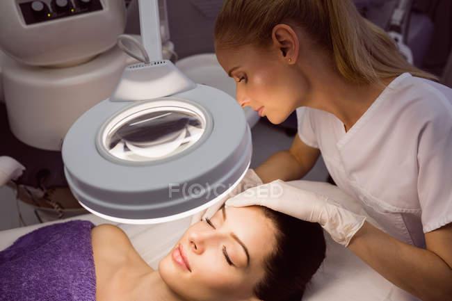 Dermatólogo examinando piel de paciente femenina en clínica - foto de stock