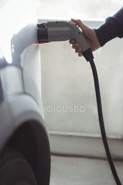 Close-up of man charging car at electric vehicle charging station — стоковое фото