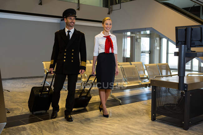 Pilot and air hostess walking with their trolley bags in the airport terminal — Stock Photo