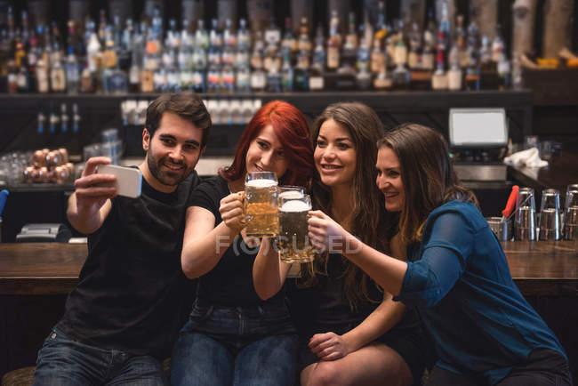Друзі проведення пивні Бокали і беручи selfie в штрих-лічильник за допомогою мобільного телефону — стокове фото