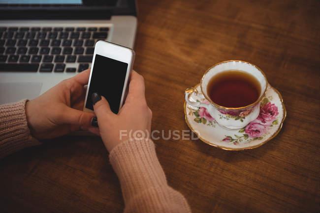 Femme utilisant un téléphone portable tout en prenant le petit déjeuner dans le salon à la maison — Photo de stock