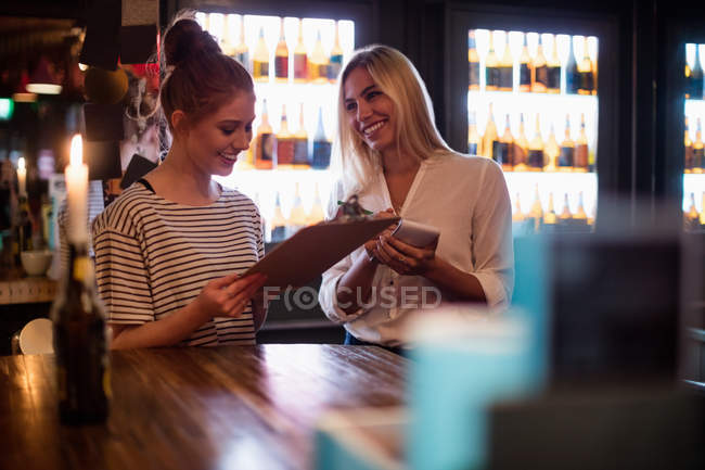 Waitress discussing the menu with woman in the bar — Stock Photo