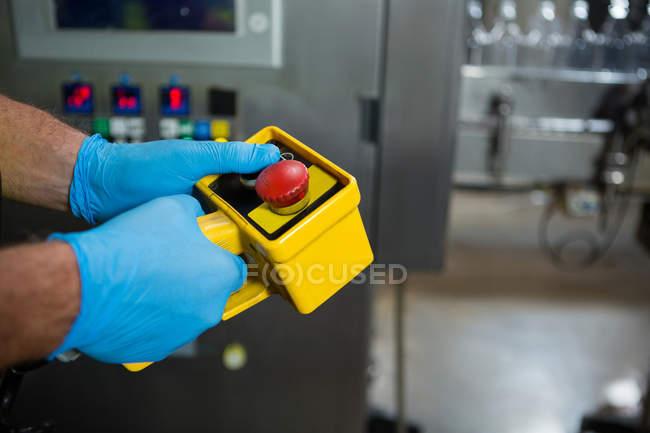 Hand des Arbeiters mit gelben Maschinen in der Fabrik zugeschnitten — Stockfoto