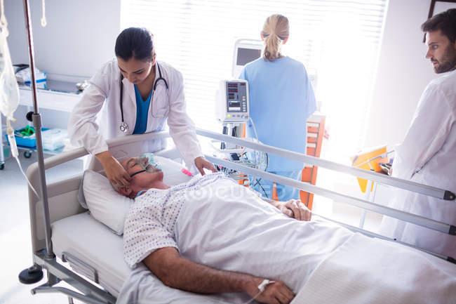 Женщина-врач поставить кислородную маску на лице больного в больнице — стоковое фото