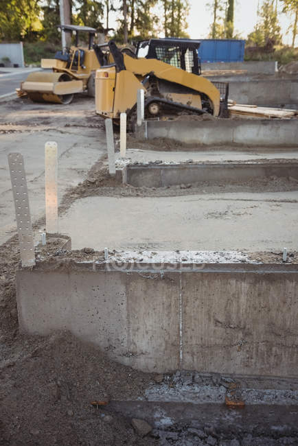 Concrete foundation and bulldozer at construction site — Stock Photo