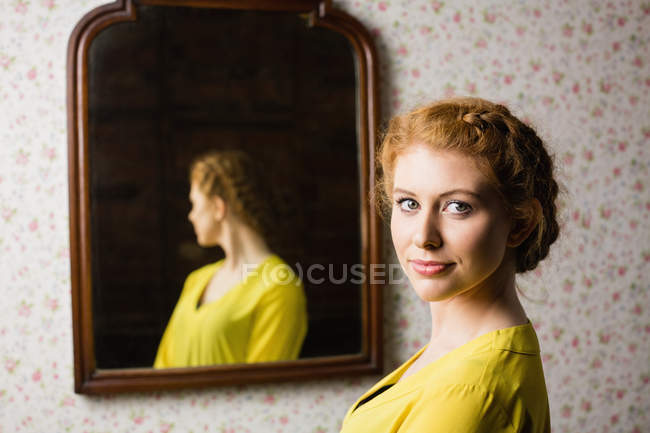 Portrait of a beautiful woman standing in front of mirror — Stock Photo