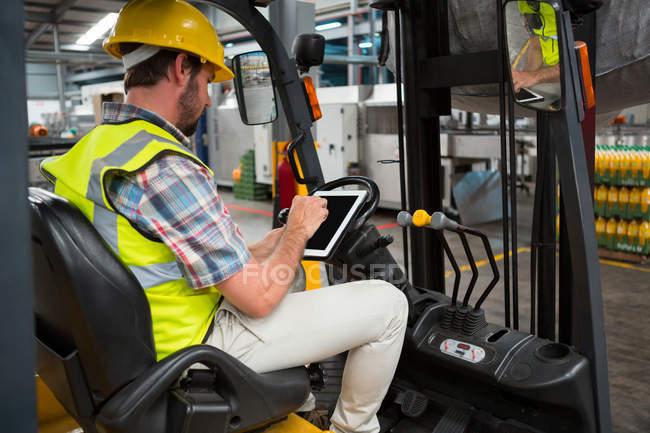 Travailleur masculin confiant utilisant une tablette numérique assis sur un chariot élévateur dans un entrepôt — Photo de stock