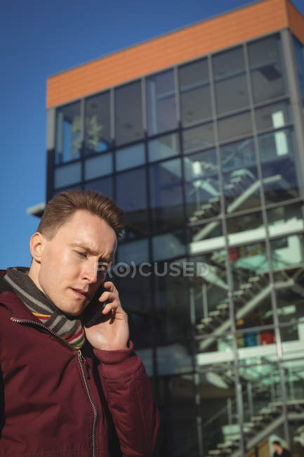 Мужчина говорит по мобильному телефону на улице перед офисным зданием — стоковое фото